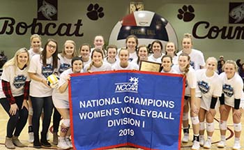 Lady Bobcats with NCCAA Division I Women's Volleyball National Championship banner