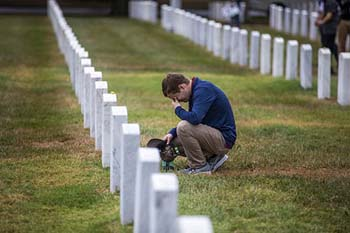 Student kneels by grave in Arlington National Cemetery